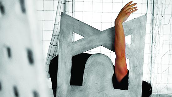 Image of a person laying down holding their arm up through a painted sculpture piece against a white checkered background.