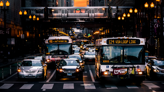 photo of street with buses and cars with subway over bridge