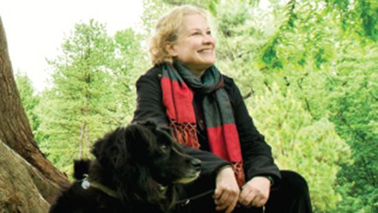 A woman and a dog with trees in the background