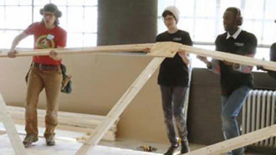 three students lifting trusses