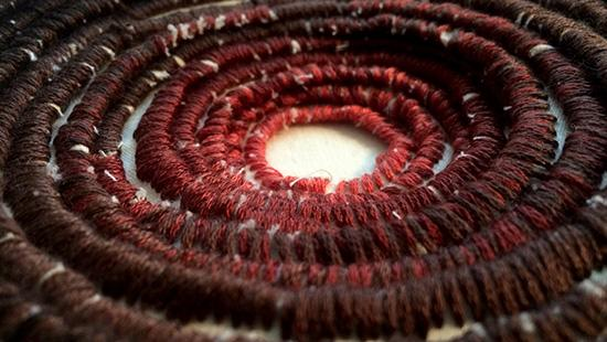 Red and brown colored string sewn together in a spiral pattern.