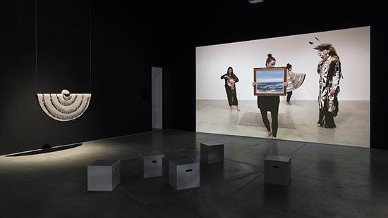 Image of 5 block sculpture pieces in front of a hanging sculpture and a large photo of 4 women, in a museum
