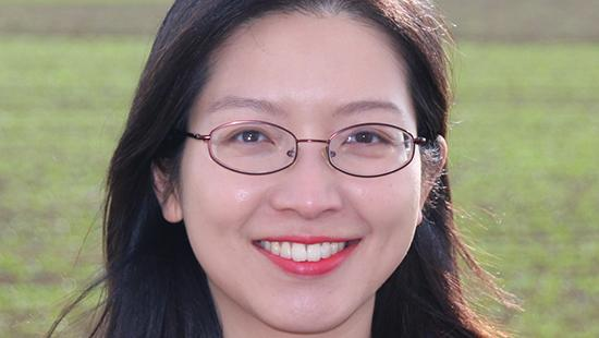 A woman smiling, wearing glasses