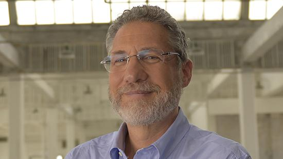 A man's face with a beard and wearing glasses against a modern architectural atrium