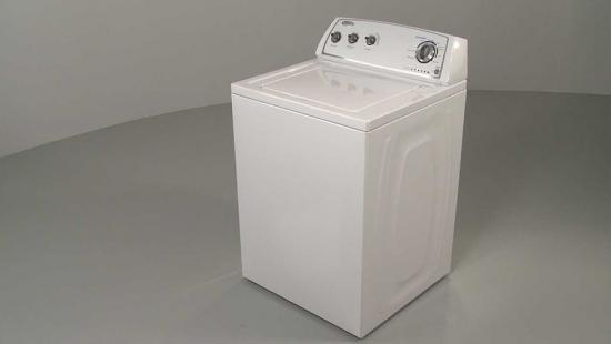 white washing machine sitting in grey space