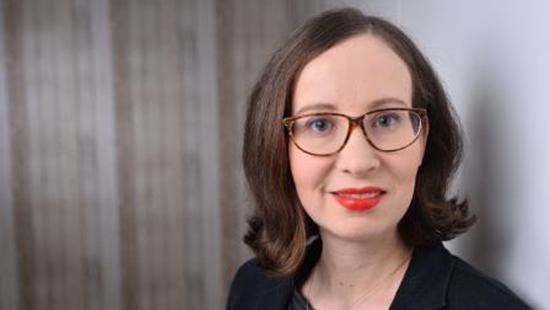 A woman's face wearing glasses and red lipstick