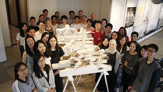 group of students around a table with an intricate white building model on it