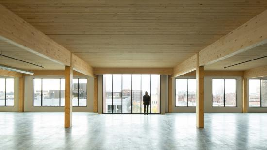 Color photo of wood truss and wood-clad ceiling interior space