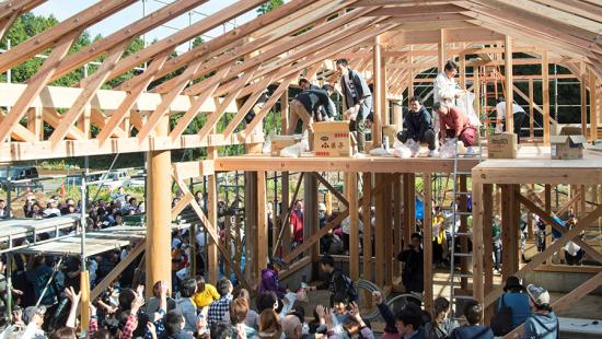 A group of individuals situated in a wood framed structure, consisting of a lower level filled with people, and loft area where fewer stand above.