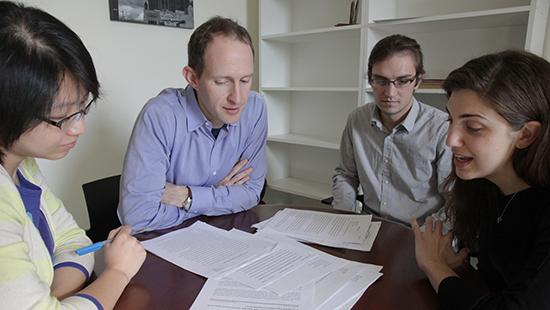 Four people sit at a round table with papers spread out in front of them.