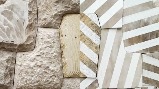 Light tan, textured stonework which alternates between unpainted stones, and stones which are covered in a series of both white and metallic gold stripes.