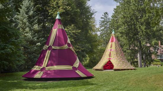 Two fabric tents, one pink and gold the other red and gold on grass surrounded by trees and a house in background.