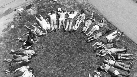 black and white photo of aerial view of women lying on the grass creating a woman symbol in 1975