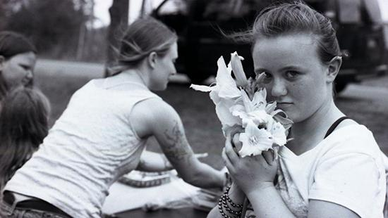 Black and white photograph of young girl holding flowers with a woman and other children in the background.