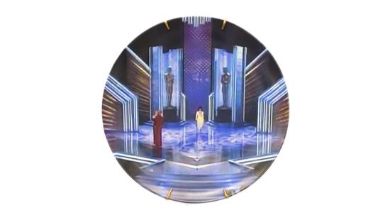 Circular image of an old Academy Awards stage with one woman walking in the middle wearing a yellow dress.