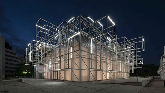 A four-story rectangular building clad with translucent panels, with metal, lighted scaffolding protruding from the upper levels and top, seen at night.