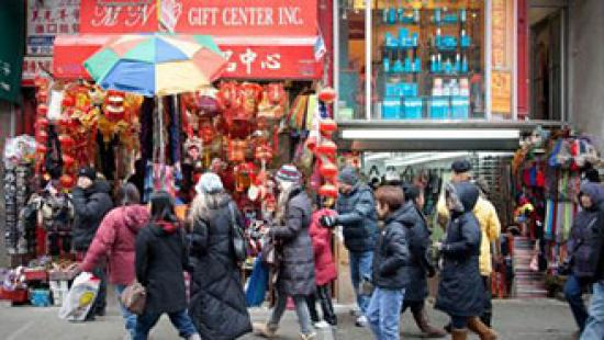 crowded street with people walking past stores in winter coats