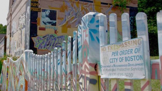 A painted fence with sign and building in background
