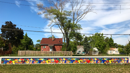 photo of mural wall with tree and sky in background
