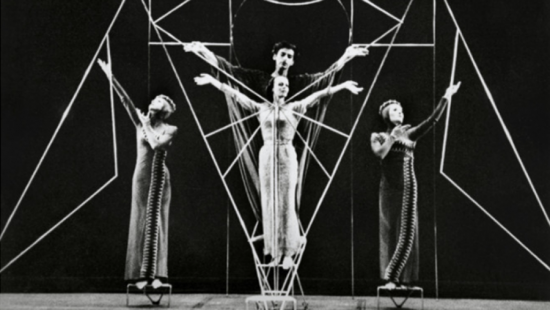 black and white image of people in a performance with abstract lines behind