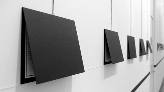 installation shot showing black folded envelopes attached to a white wall