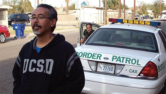 Man standing near the road with a border patrol agent getting out of her car.