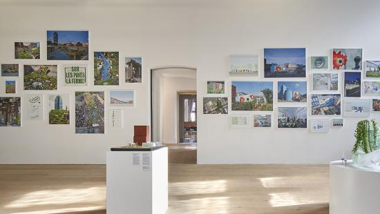 The interior of a modern gallery space. Images are hung on the walls and models are displayed on white podiums varying in size.