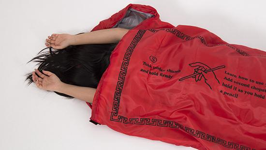 Image of someone with long dark hair and arms sticking out of a chopsticks wrapper sleeping bag.