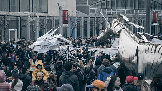 a crowd of people around a white dragon sculpture and a metal unicorn sculpture