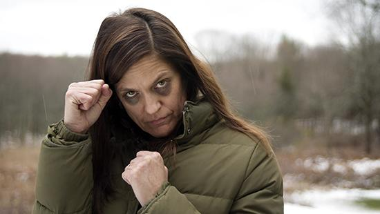 Woman standing outside wearing a winter coat with fists raised and two black eyes.