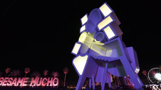 Large interactive sculpture installation that is illuminated with purple and yellow light