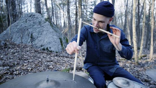 Man wearing blue clothes and a blue hat in the woods, holding a drumstick in his mouth and placing one on a cymbal.