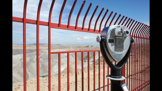 A canyon, a red fence, a viewfinder telescope, blue sky.