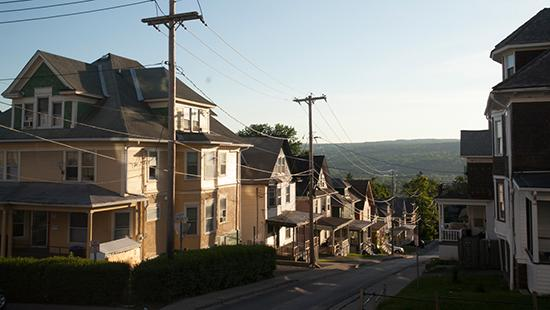 View of a row of apartment houses with power lines in front, looking down a hillside street in a suburban area.