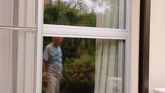 Photograph of a man's reflection in a window pane.