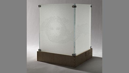 Two panes of glass with a face sketched intricately across held together by metal pieces in the corners and sitting on a wooden crate.