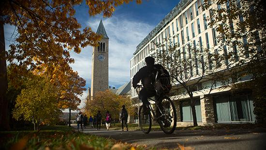 A student bikes past Olin Library in fall, with McGraw Tower in the background.