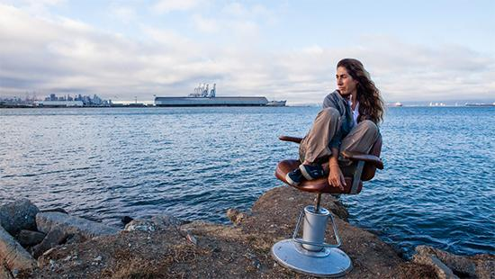 woman sitting in a swivel chair on the shore with large ships in the background