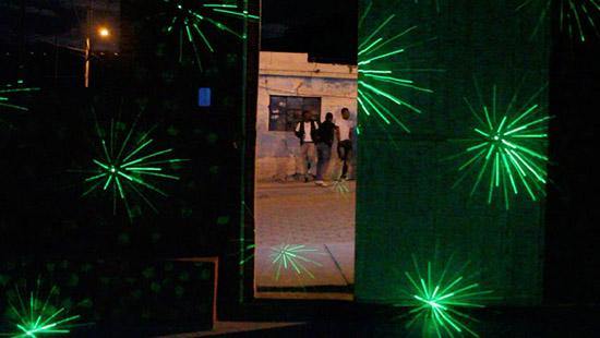 Three men leaning outside against a wall with the viewer looking at a dark room with bright green laser lights shining out.