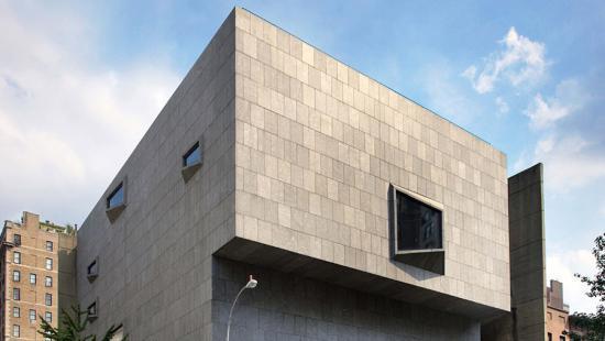 Corner of a gray stone building, small windows, blue sky.