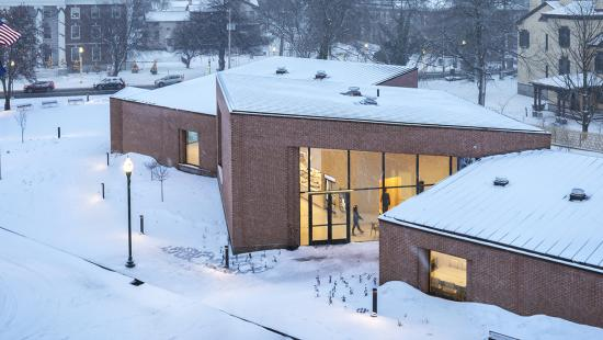 Modern brick building surrounded by snow, illuminated from the inside through the buildings windows