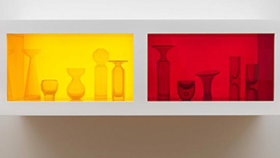 Photograph of glass objects in an enclosed shelf lit with yellow and red light.