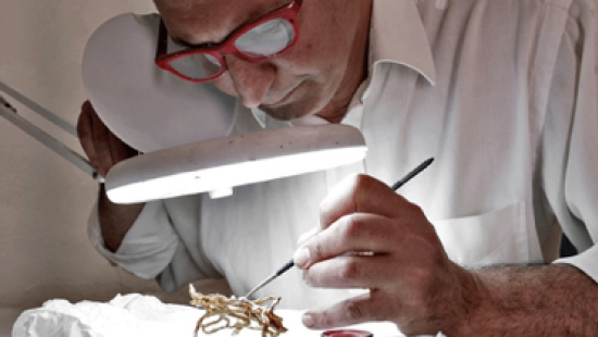 A man painting a small sculpture under a magnifying lamp
