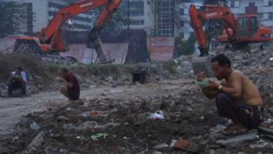 Men squatting while eating at a demolition site
