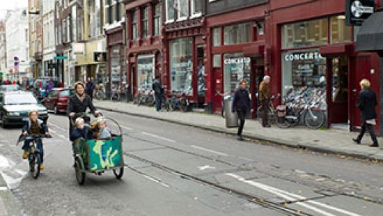 Mother and children biking in city street