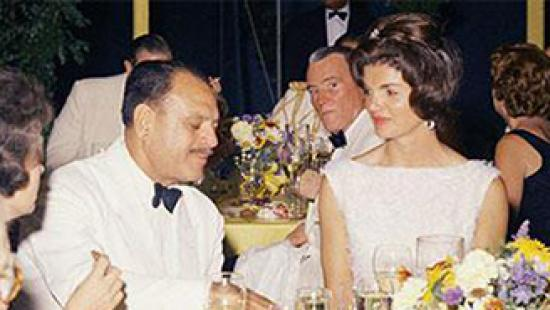 Photograph of Jacqueline Kennedy dining with some people.