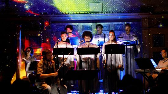 Ten people singnig and playing instruments are lit by colored lights on a dark stage.