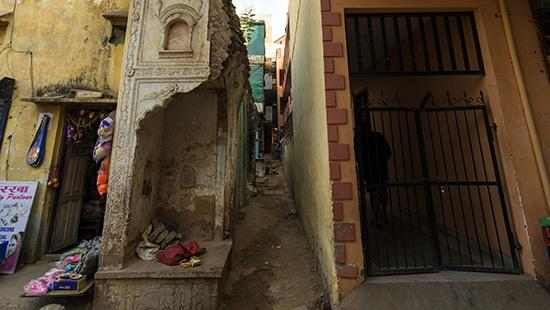 a narrow byway and a gated doorway near crumbling walls in an Indian city