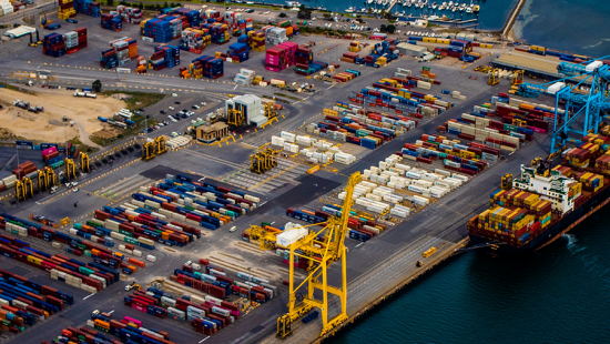 shipping yard with yellow and blue cranes along a body water