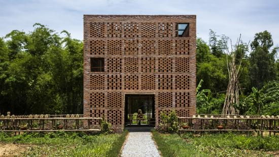 square building made of terra cotta with small decorative square sections surrounded by forest